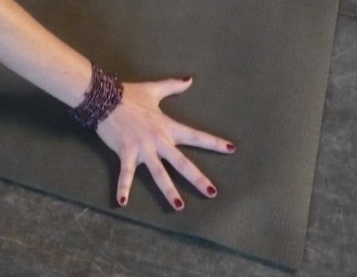 Fingers spread on a yoga mat.