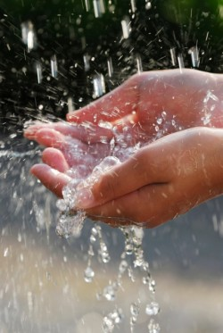 The Power of Receiving: Open hands receiving pouring water