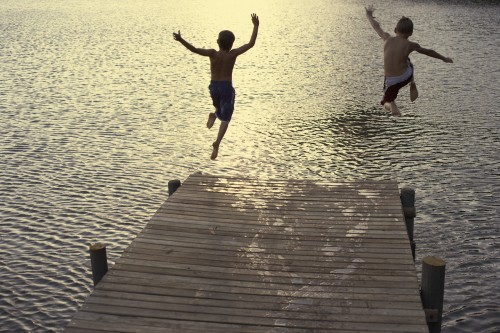 Two Boys Diving off Dock into Lake