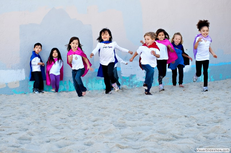 Kids in capes on the beach