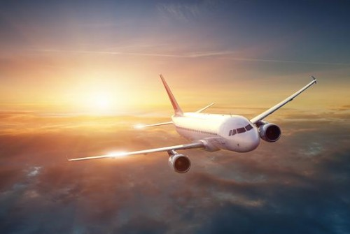 Airplane in the sky at sunset via fotolia