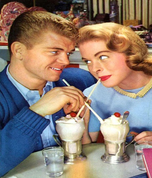 vintage couple sharing milkshakes