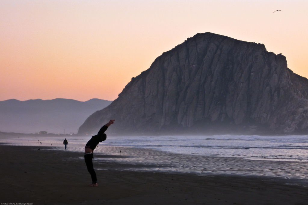 "Upward Salute – Urdhva Hastasana - Person performs mystical ""Sun Salutation"" yoga stretching exercise on Morro Strand ""Church of Kelp"""