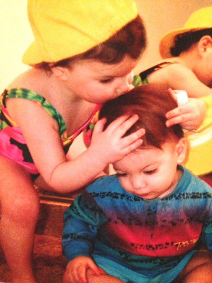 A young Alexandra Samit places a kiss on a young Ben Samit's head, her little brother