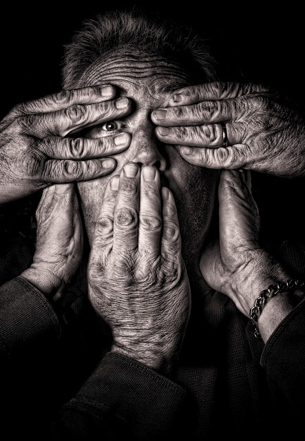 older person wrinkles hands face eye see no evil