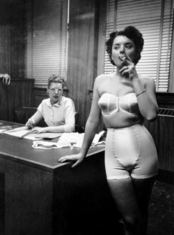 Lingerie model smoking in an office, Chicago, 1949