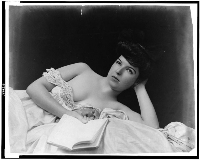 Young_woman,_wearing_negligee,_lying_in_bed,_holding_book