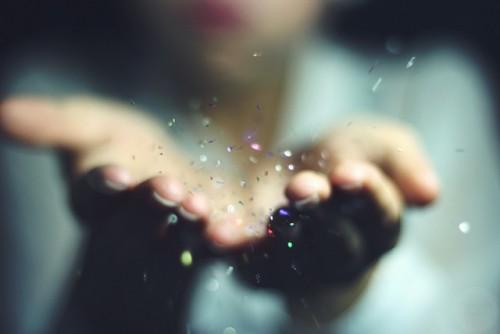 woman hands blowing glitter