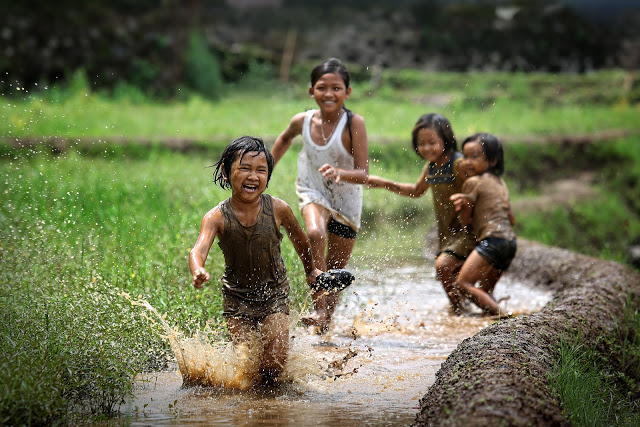 girls kids playing in mud laugh friends