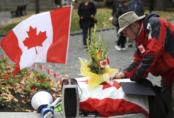 A man writes in books of condolences to fallen Canadian soldiers, Warrant Officer Patrice Vincent and Corporal Nathan Cirillo, during a vigil in Montreal