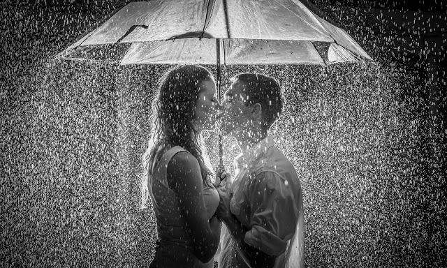 couple kissing rain umbrella