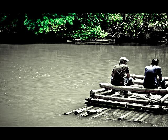 two friends sitting on a raft listen