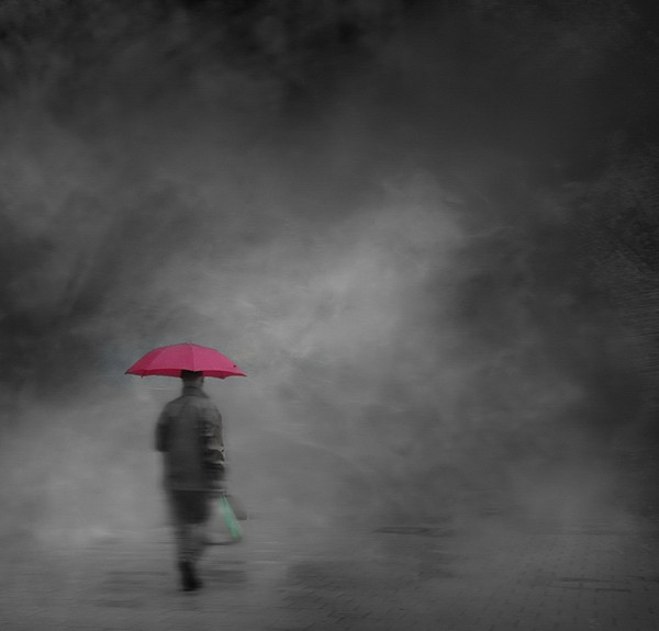 Man alone in fog with pink umbrella