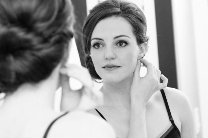Woman_wearing_earring_in_front_of_mirror