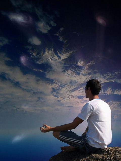 man meditate cliff sky clouds