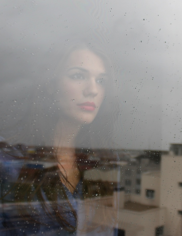 woman sad reflection window rain
