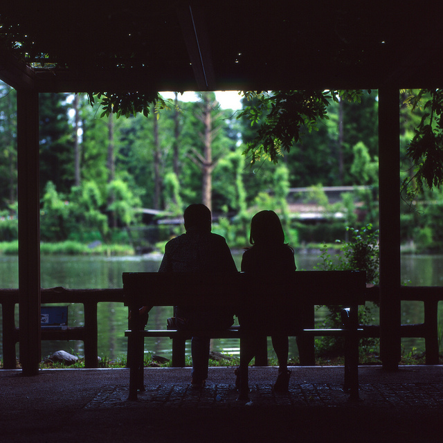 couple silhouette park bench