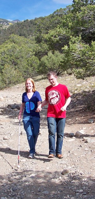 Mel and Jordan walking sighted guide down the cleaner side of a mountain trail.