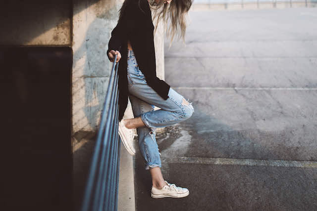 woman-leaning-wall-casual-waiting-thinking-style