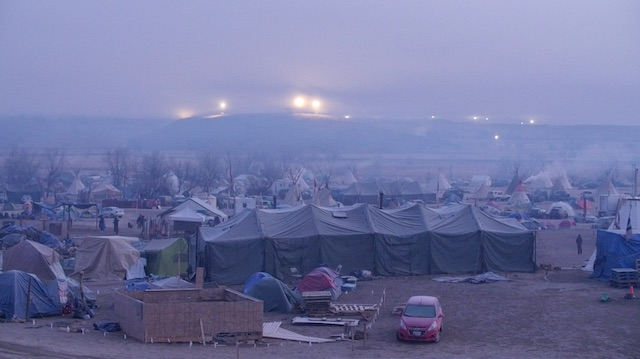 This photo shows the Oceti Sakowin Camp at Standing Rock Indian Reservation in 10 degree temperatures on Nov. 19, 2016. The stadium spotlights in the distance were erected by Energy Transfer Partners to illuminate the Dakota Access Pipeline as part of their militarized security measures.